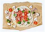 Une cru pizza au salami et champignons sur papier sulfurisé