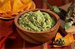 Guacamole in eine hölzerne Schüssel; Tortilla-Chips; Verkohlten Jalapeno Peppers
