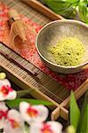 Japanischer Matcha-Grüntee-Pulver in einer Schüssel auf Tablett; Blumen