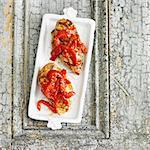 Deux grillée garnie de poivrons rouges sur un plat de blanc de poulet
