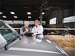 Farmer and veterinarian talking by barn