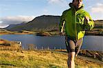 Hiker running up grassy hillside