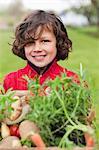 Garçon heureux avec une caisse de légumes « maison »