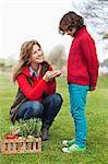 Femme montrant des légumes à son fils