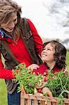 Mère et fils avec une caisse de légumes « maison »