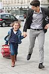 Mädchen ziehen ein Reisetrolley und führen Sie mit ihrem Vater
