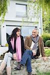 Couple romantique assis dans un jardin et souriant