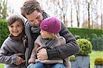 Man hugging his two children