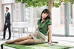Businesswoman relaxing on grass mat