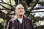Senior man by tree trunk, looking away