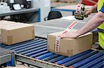 Man packing cardboard box in warehouse