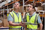 Men in warehouse using digital tablet