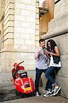 Couple de scooter, regardant de téléphone cellulaire