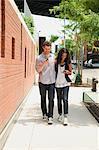 Couple en descendant la rue, regardant les téléphones cellulaires