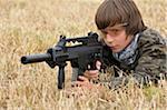 Garçon couché au sol visant les armes à feu
