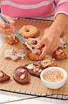 Ein Mädchen Kekse mit Puderzucker dekorieren