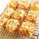 Guimauves maison recouvertes de noix de coco grillée sur un support de refroidissement