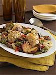 Cuisses de poulet rôti avec pommes de terre, les oignons et les poivrons dans un plat de service