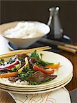 Boeuf et brocoli sauté avec du riz blanc avec des baguettes