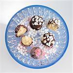 Petit Fours mit Schokoladenglasur, Zucker-Perlen und Schneeflocken