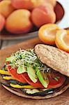 Vegetarische Sandwich mit gegrillter Aubergine, Zucchini, gelbe Paprika, Tomaten und Avocado auf eine flache Runde Roll