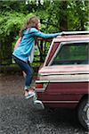 Teenage Girls Hanging on to Back of Car