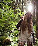Jeune femme en forêt avec Sun Behind Head