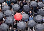 Debout de parapluie rouge dehors dans la foule des gens d'affaires
