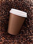 Gros plan d'une tasse de café brun sur le dessus de grains de café