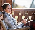 Femme souriante avec papier et crayon sur le porche de la cabine