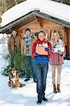 Portrait of smiling Paare und Hund mit frisch geschnittenen Weihnachtsbaum und Geschenke vor der Hütte