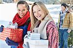 Portrait of smiling Freunde mit Weihnachtsgeschenke im Schnee