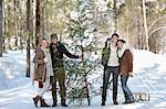 Portrait of smiling Paare mit frisch geschnittenen Weihnachtsbaum und Schlitten im verschneiten Wald