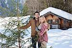 Portrait de couple avec frais coupé arbre de Noël en face de la cabine de sourire