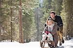 Mann schob Frau auf Schlitten im verschneiten Wald