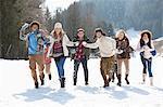 Amis souriants, jetant des boules de neige dans le champ