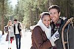 Portrait of smiling Paar mit Schlitten im verschneiten Wald