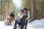 Lächelnde Paare Rodeln im verschneiten Wald