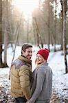 Portrait of smiling paar halten Hände im verschneiten Wald