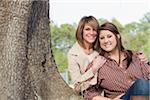 Porträt von Mutter und Tochter sitzen am Baum