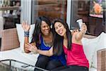 Zwei Frauen, die die Selbstbildnis mit Handy