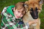 Boy Hugging Alsatian Puppy