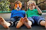 Deux garçons portant des masques se trouvant sur le Trampoline