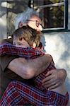 Older man hugging grandson outdoors