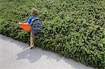 Boy walking by shrubs outdoors