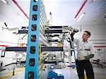 Travailleur en inspectant le gabarit de mesure pour les pièces automobiles dans une usine automobile