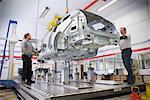 Travailleurs, plaçant la carrosserie sur la machine dans une usine automobile à mesurer