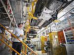 Travailleur inspecter sous la carrosserie en usine automobile