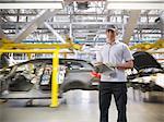 Portrait du travailleur avec les voitures sur la ligne de production en usine automobile