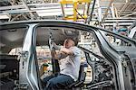 Travailleur montage Garniture de pavillon en voiture dans une usine automobile